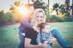 woman holding baby sitting on green grass field under sunset