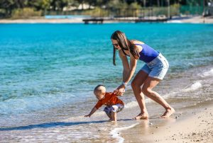 woman in blue and white tank top holding baby in white onesie on beach during daytime