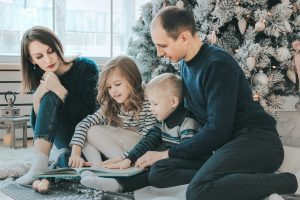 girl and boy reading book sitting between man and woman beside Christmas tree