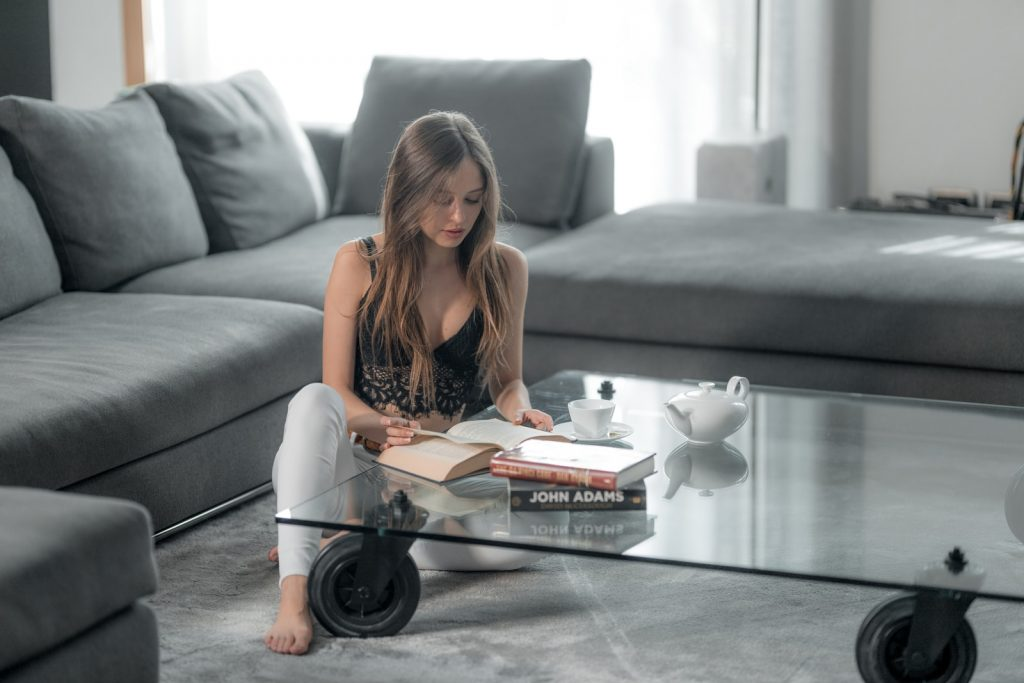 woman in orange tank top reading book on gray couch